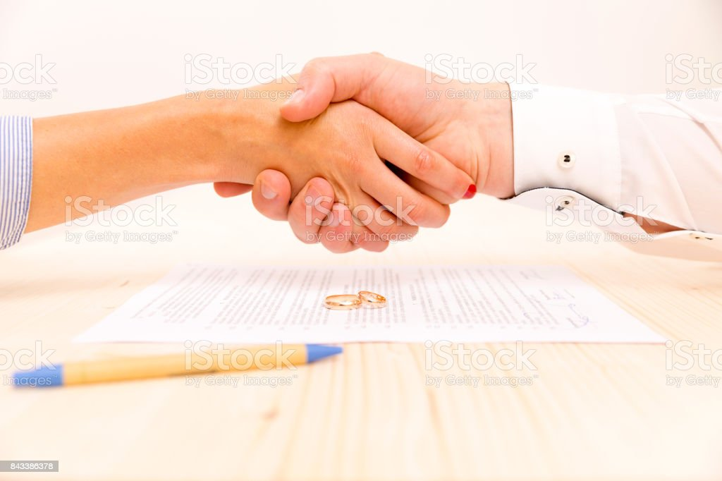 Closeup of a young man an a young woman signing a prenuptial agreement stock photo