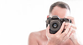closeup of a young man focusing and looking through the viewfinder of his reflex camera taking a picture. copy space