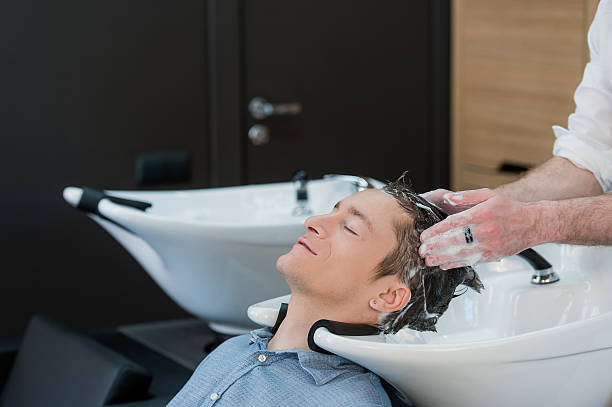 Close-up of a young man having his hair washed stock photo