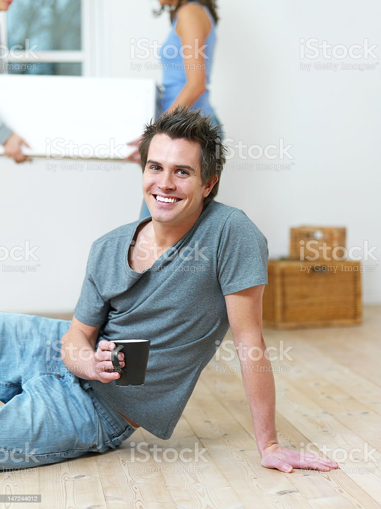 Close-up of a young man relaxing on floor having coffee royalty-free stock photo