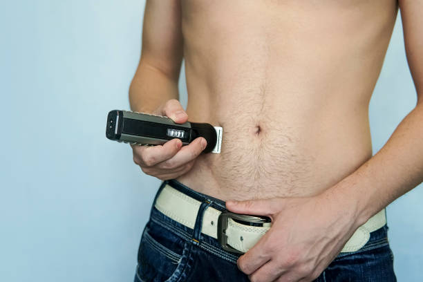 closeup of a young man trimming the hair of his pubis with an electric trimmer. concept of a clean healthy body for men. man haircut pubic hair with a clipper. - body shaver men s and pictures Factors To Keep In Mind Before Choosing The Best Body Groomer