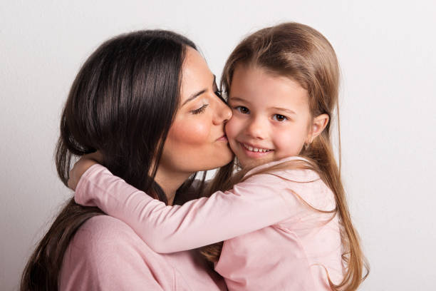 A close-up of a young mother kissing her small daughter in a studio. stock photo