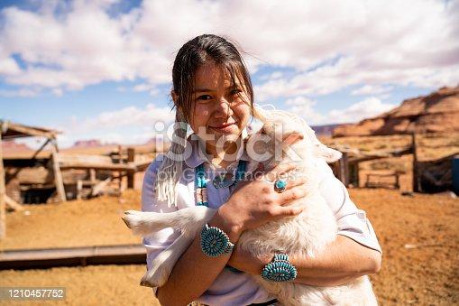 A teenage Navajo girl holding her pet lamb