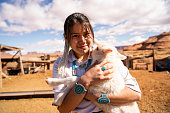 istock Closeup Of A Young Navajo Woman Holding A Lamb From The Flock 1210457752