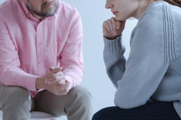 nahaufnahme einer jungen traurige frau teilen ihre trauer mit einem psychotherapie-spezialisten bei einer einzelberatung treffen. - trauer verlust stock-fotos und bilder