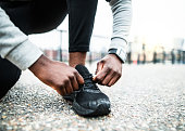 A close-up of an unrecognizable young sporty black man runner tying shoelaces before running outside in a city.