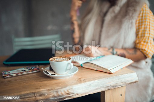 1183295518 istock photo Close-up of a young tattooed woman writing in the coffee bar 973862066