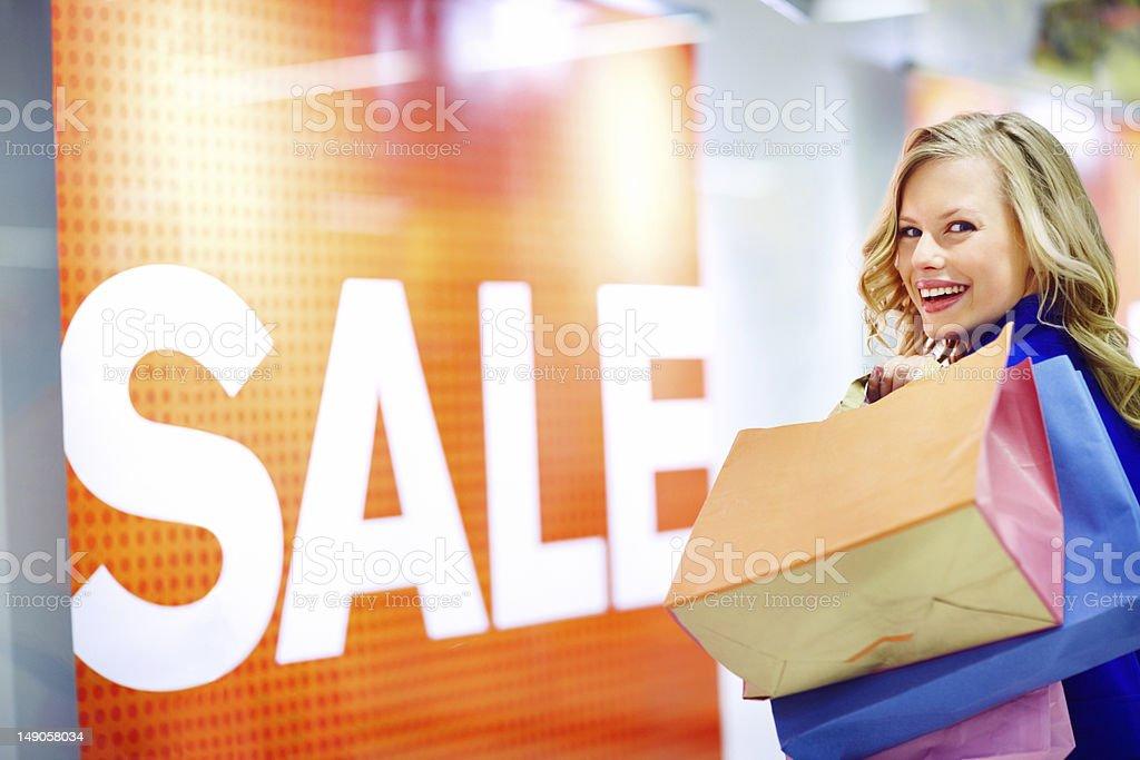 Close-up of a young woman carrying shopping bags and smiling royalty-free stock photo