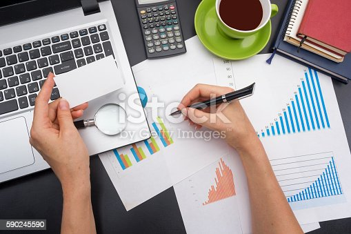 istock closeup of a young woman checking accounts. Office desk table 590245590