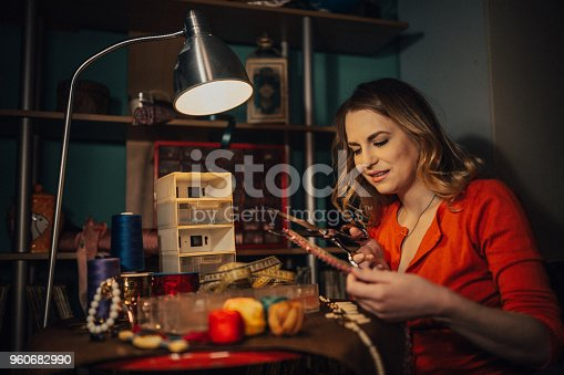 512345816istockphoto Close-up of a young woman cutting materials to make jewelry in the workshop 960682990