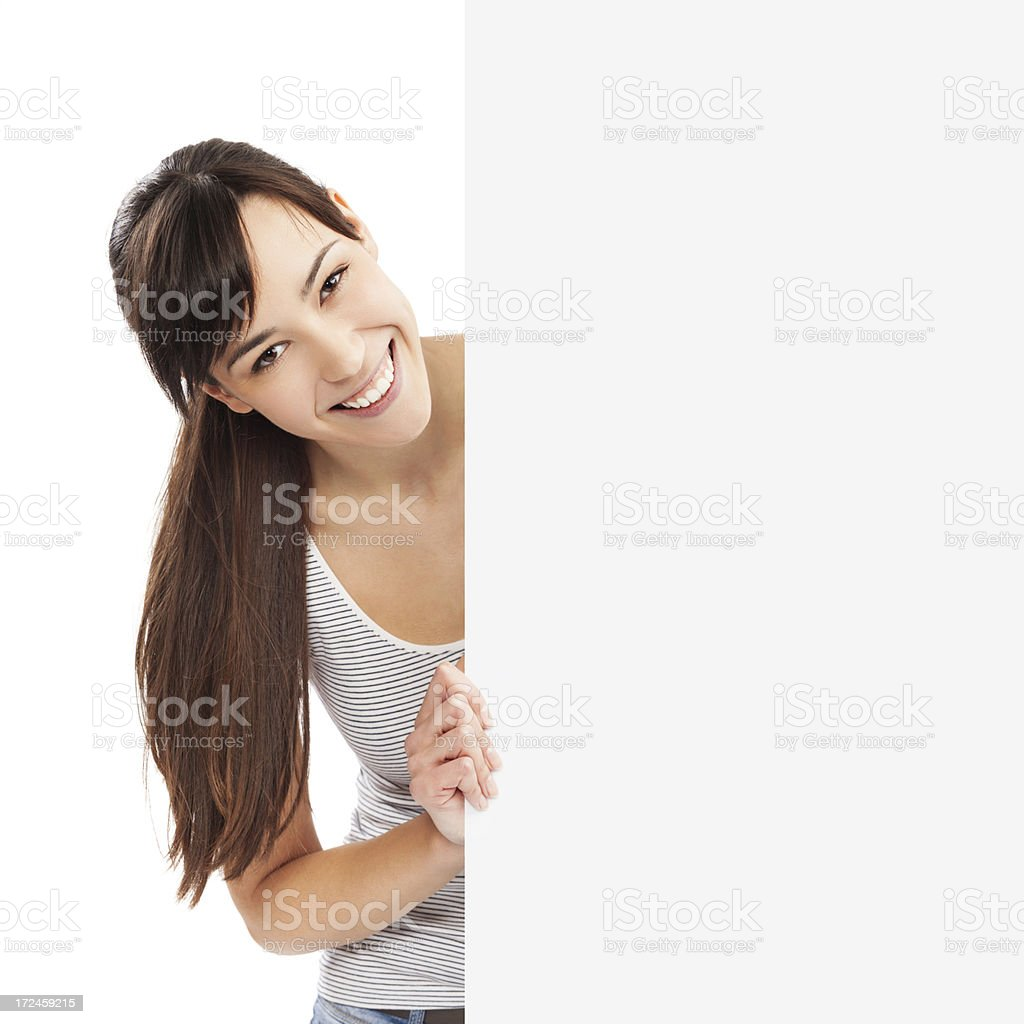 Close-up of a young woman leaning from behind billboard royalty-free stock photo