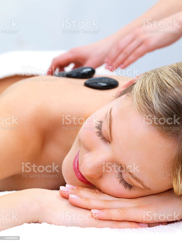 Close-up of a young woman receiving hot stone massage royalty-free stock photo