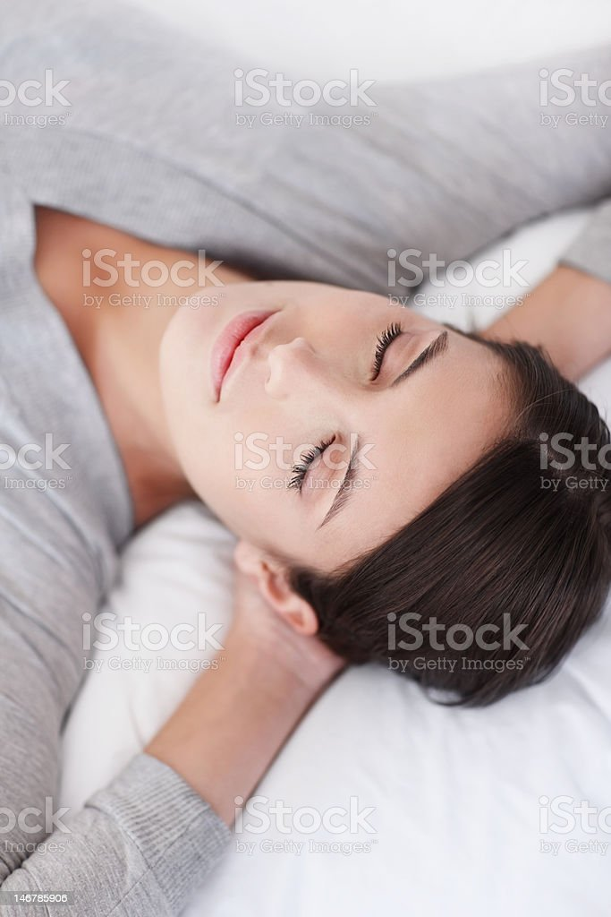 Closeup of a young woman with eyes closed on bed royalty-free stock photo