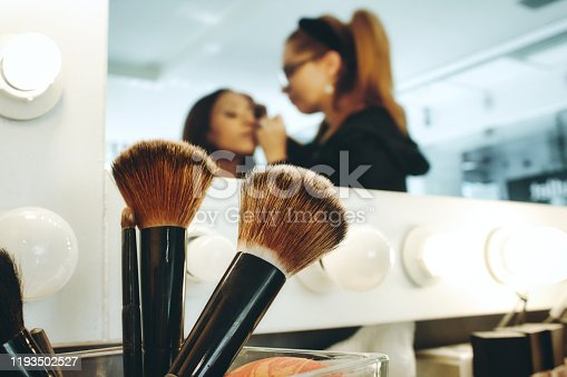 istock Closeup of accessory brushes with a professional make-up artist in a studio painting a woman's face 1193502527