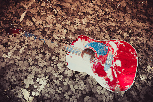 istock Close-up of acoustic guitar lying on a woodland, vintage style with copy space 968903640