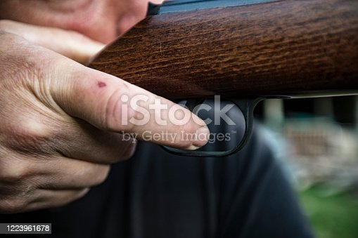 Close-up of Adult Man Aiming With Air Gun.