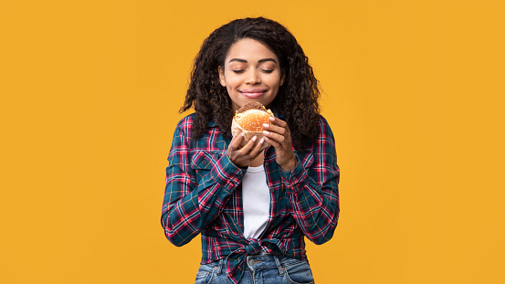 Delicious Meal. Portrait Of Hungry Black Female Model Eating Burger. Smiling African American Woman Holding And Smelling Tasty Fast Food, Isolated Over Orange Studio Background, Banner, Copy Space