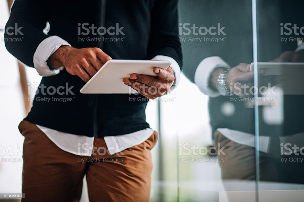 Close-up of African-american professional Entrepreneur typing on tablet. stock photo