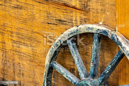 Close-up of age weathered wagon wheel with wooden spokes leaning against a yellow wooden box, abstract