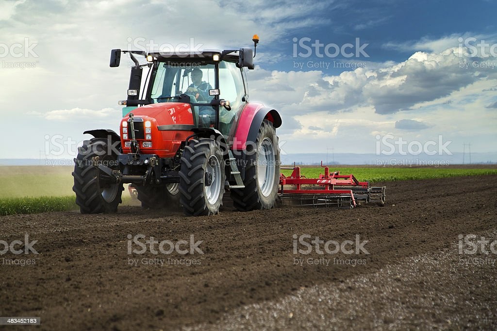 Close-up of agriculture red tractor cultivating field over blue sky stock photo