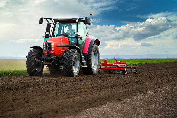 Close-up of agriculture red tractor cultivating field over blue sky Close-up of agriculture red tractor cultivating field over blue sky machinery stock pictures, royalty-free photos & images