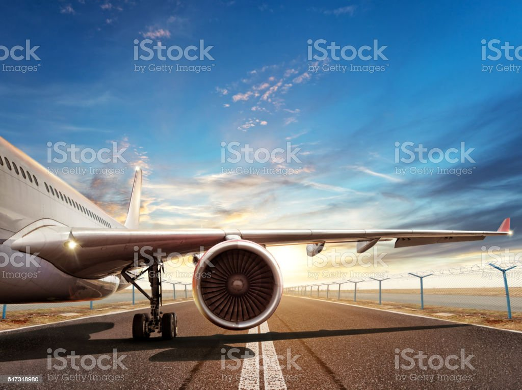 Close-up of airplane on runway in sunset light stock photo