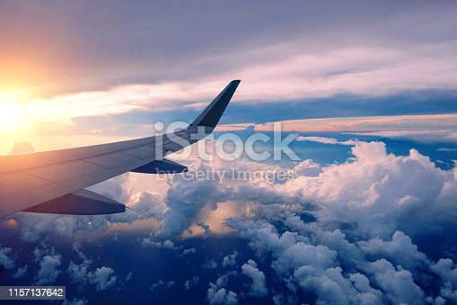 Close-up of airplane wing flying at sunrise