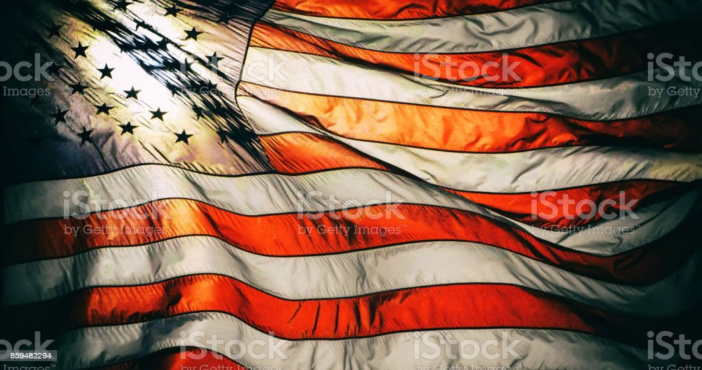 Closeup of American flag on flag pole waving in the wind. stock photo