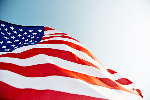 Close-up of American flag waving against blue sky.