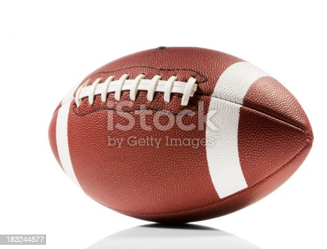 A brown and white american football isolated on a white background with a clipping path. The ball casts a soft shadow on the white background. The leather forms a pitted texture and the ball has white lines painted around it with white laces across the middle.