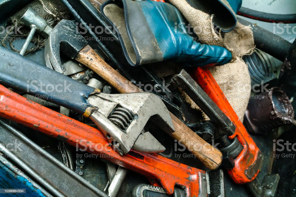 Close-up of a pile of dirty, scratched, well-used tools, including...