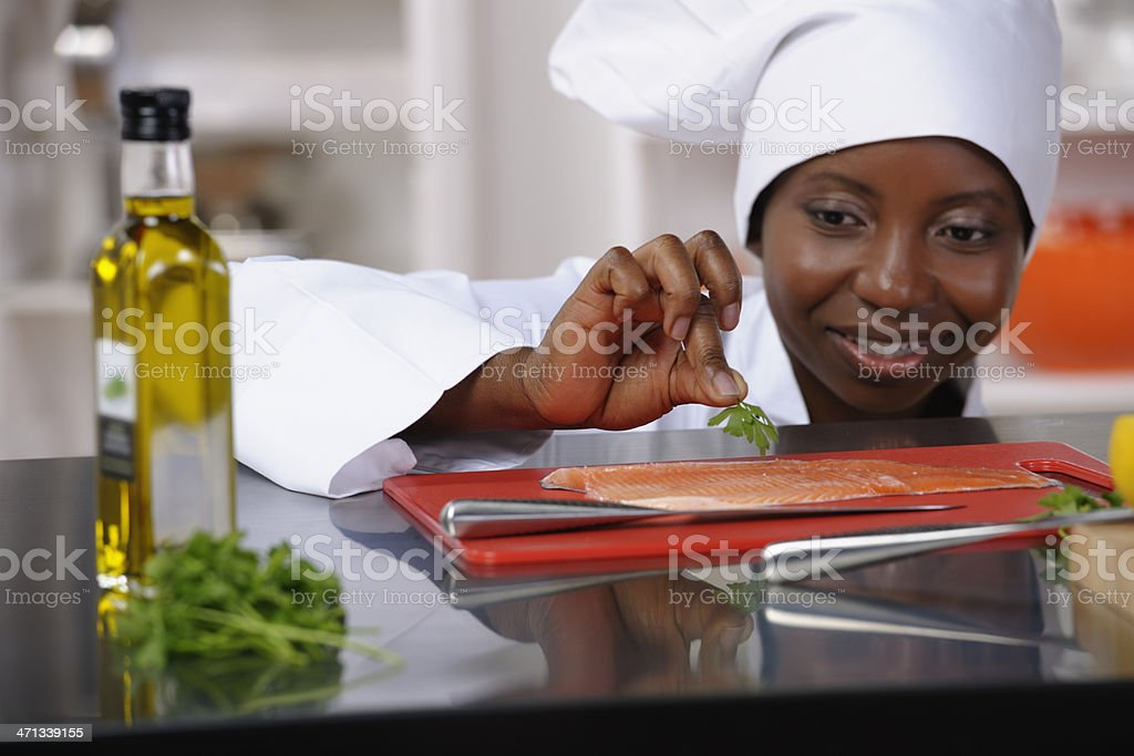 Close-up Of An African American Female Chef Preparing Fish royalty-free stock photo