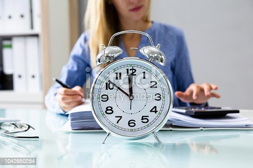 istock Close-up Of An Alarm Clock On Reflective Desk 1042650254