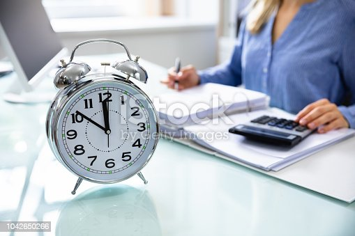 istock Close-up Of An Alarm Clock On Reflective Desk 1042650266
