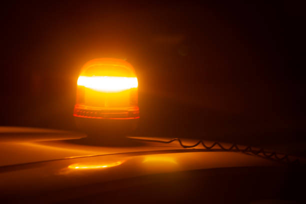Closeup of an amber strobe warning light on the roof of a car at night stock photo