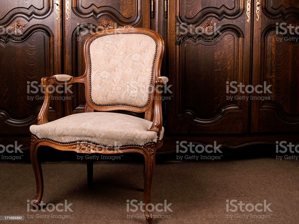 A close-up of an antique cream colored armchair stock photo