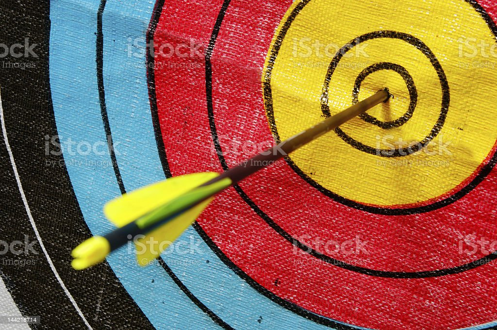 A close-up of an arrow on the center of a colorful target stock photo