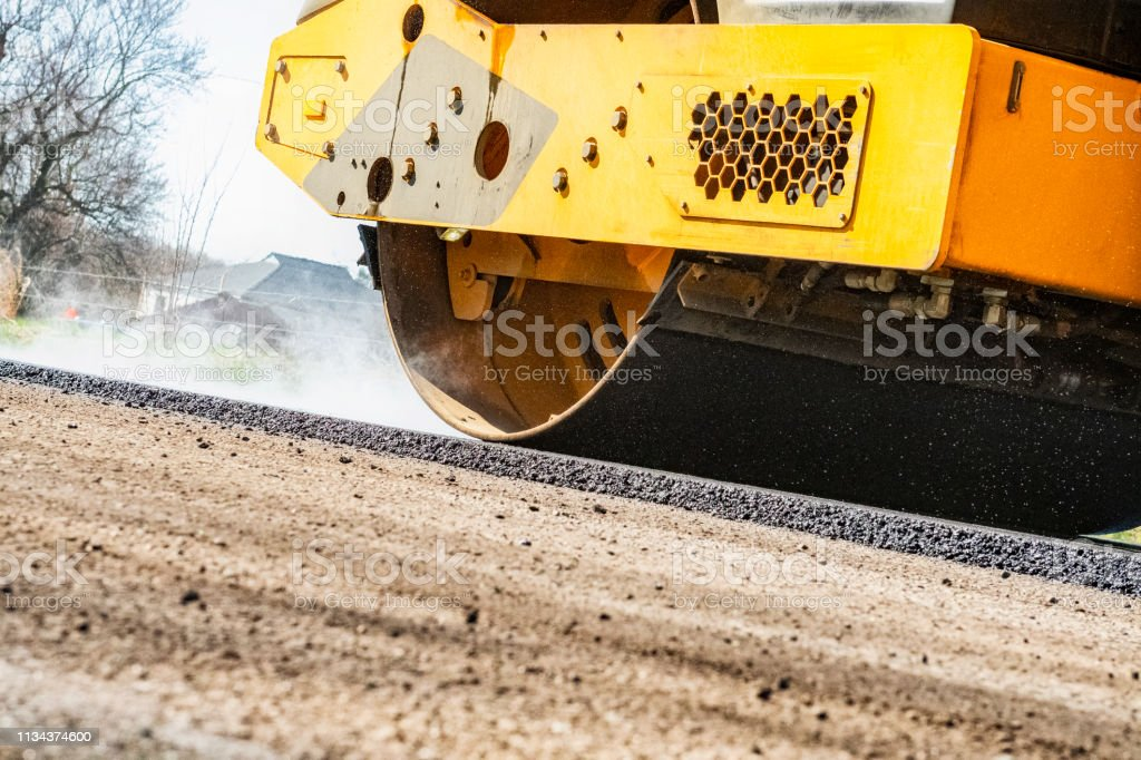 A close-up of a yellow vibrating asphalt compactor compacting the...