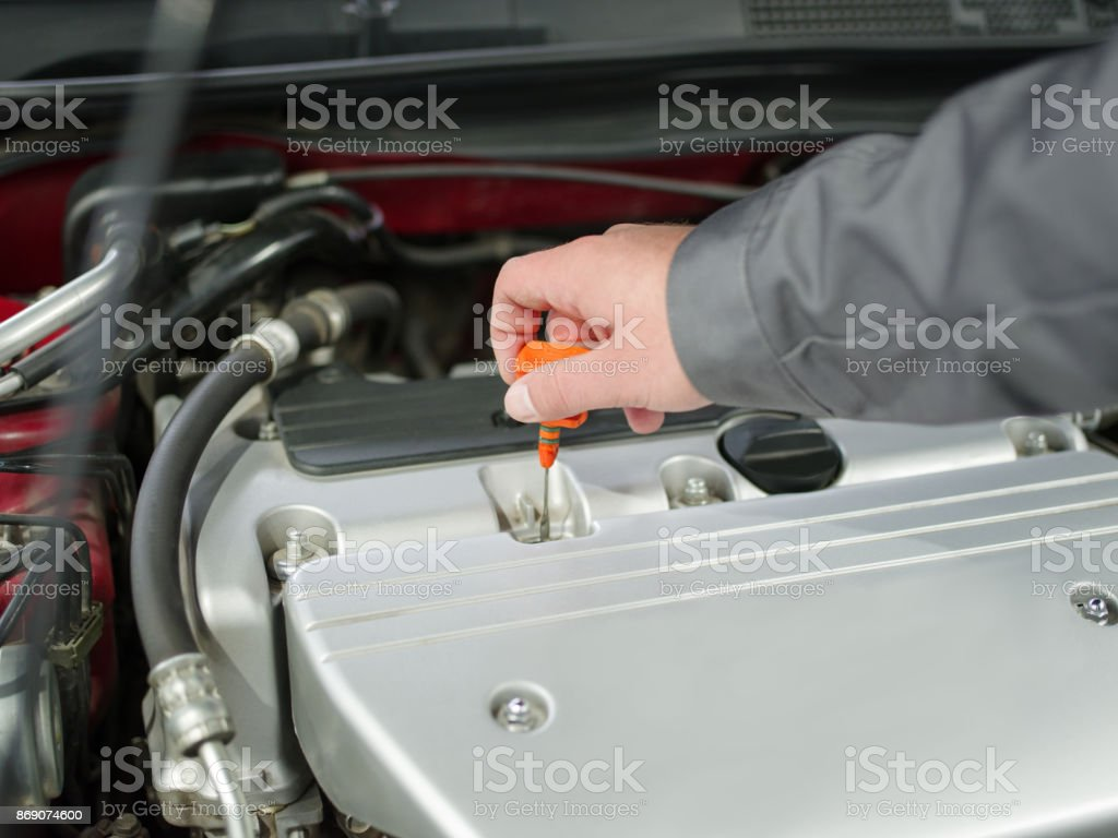Close-up of an auto mechanic examines the oil in the car stock photo