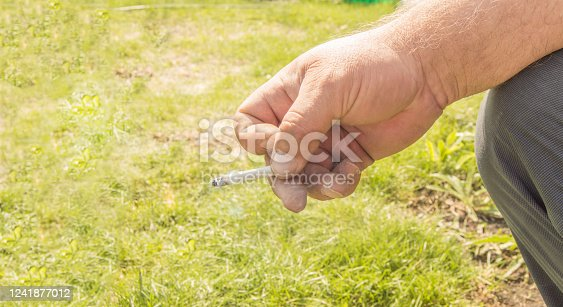 Close-up of an elderly man's hand holding a cigarette and Smoking against an open nature bokeh. Concept of harm of Smoking, Smoking cessation.