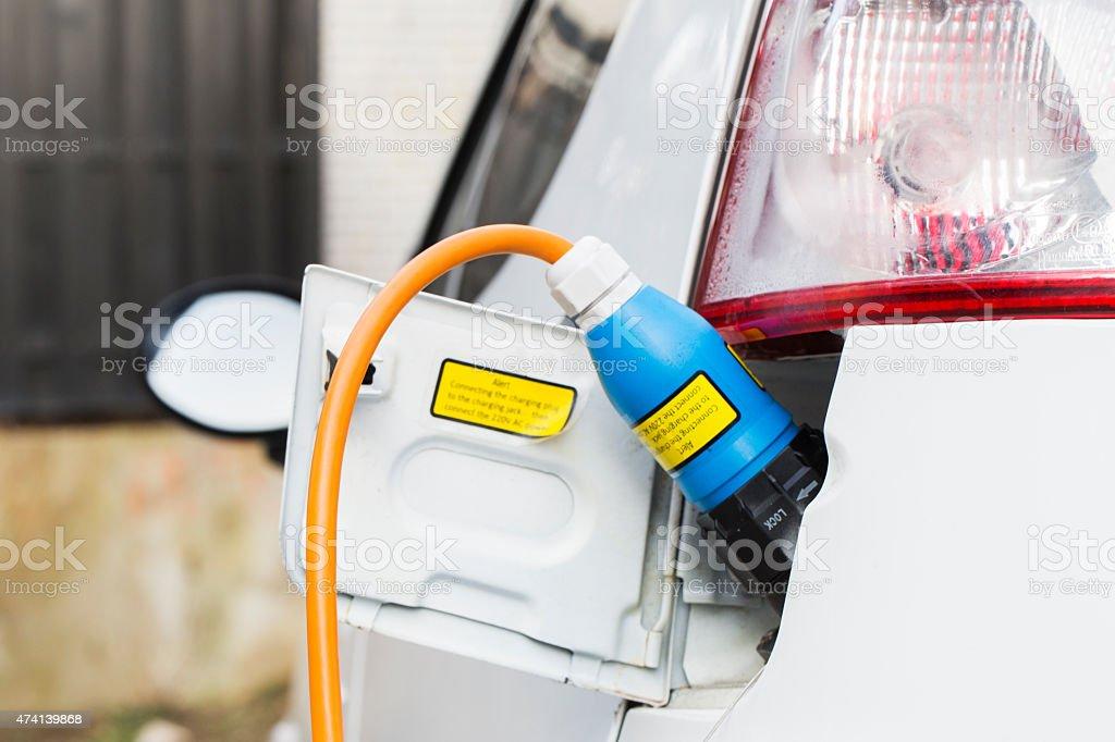 Closeup of an electric car plug while recharging stock photo