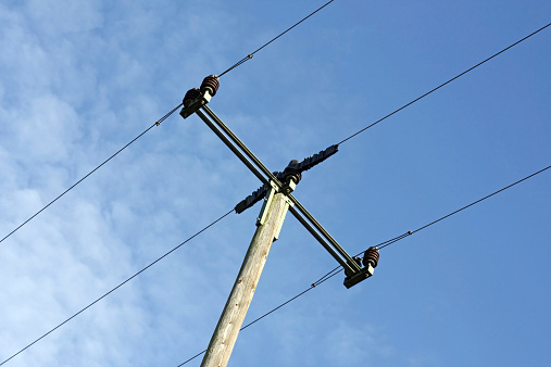 Closeup of an electricity pylon against the bright sky