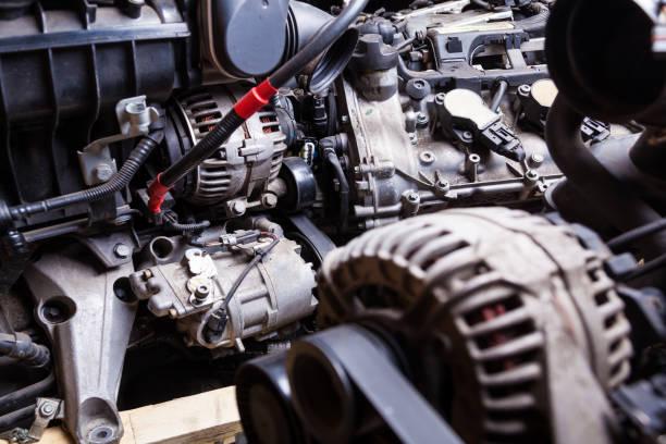 在汽車服務的黑暗中,用發電機和附件在金屬部件背景上關閉發動機。零件商店或車間的背景。圖像檔