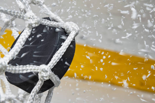 close-up of an ice hockey puck hitting the back of the net as snow flies, side view - hockey foto e immagini stock