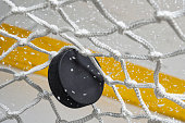 A close-up view of an Ice Hockey puck hitting the back of the goal net as shavings fly by, viewed from the front. Scoring a goal in ice hockey.
