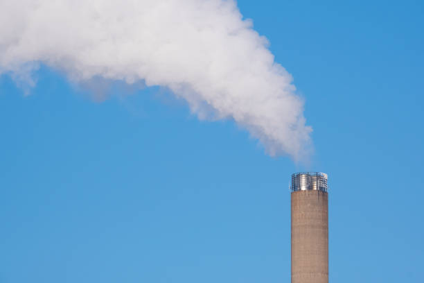 A closeup of an industrial smoke pipe against clear blue sky. stock photo
