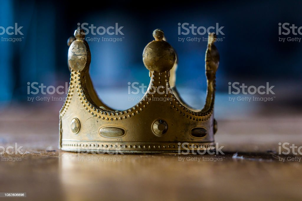 Close-up of an isolated, fake, plastic, worn-out gold imitation crown with nice dark blue bokeh. stock photo