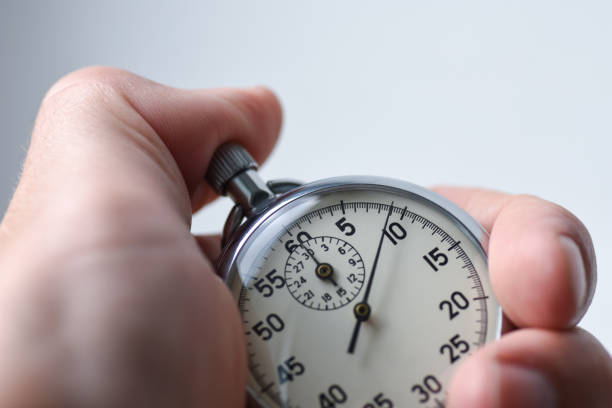 A close-up of an isolated hand presses the stopwatch start button in the sport, measurements, metrology stock photo