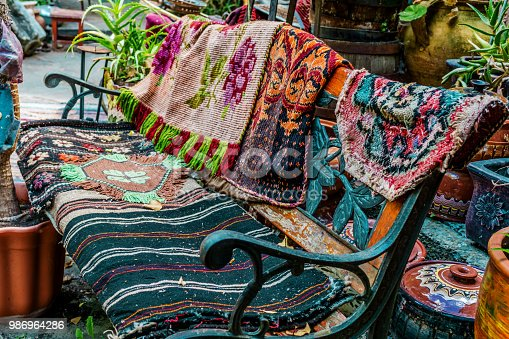 istock Close-up of an old bench covered with woven scarves and rugs. Ethno motifs - boo chic, natural woven fabrics. Shallow depth of focus, bareback background. 986964286