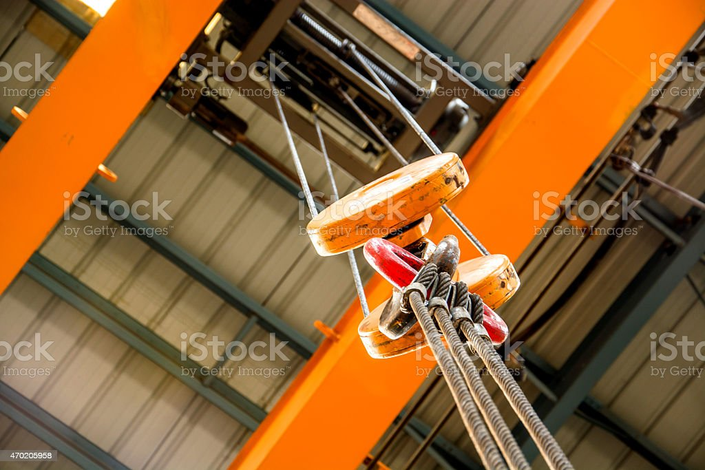 Close-up of an orange crane pulley over an orange ceiling stock photo